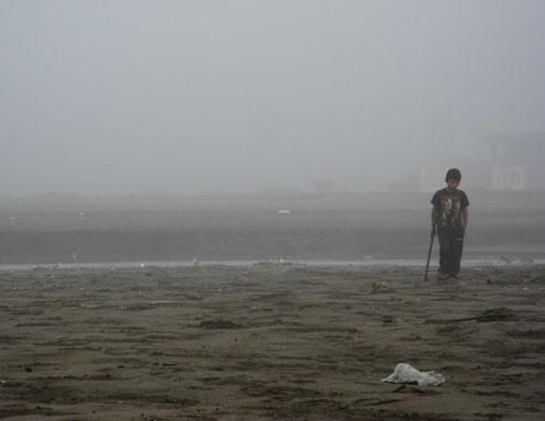 Poiss rannas eelmise öö peost jäänud prügi sorteerimas